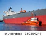 A Orange Tugboat Assisting A...