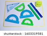Small photo of Corner ruler, green and blue protractor rulers and a pencil sharpener on a white background.