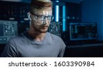 Portrait of Software Developer / Hacker Working on Computer, Projected Code Numbers and Characters Reflect on His Face. Dark Room Full of Electronics, Computers, Displays. Hacking or Programming - stock photo