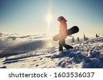 Female Snowboarder Holding...
