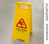 Small photo of Sign showing warning of wet floor on wet floor. Wet floor caution sign on pathway in office.