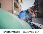 Woman Is Cleaning An Icy Windo...