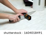 Woman Sharpening A Knife With A ...