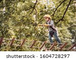 Small photo of Balance beam and rope bridges. Go Ape Adventure. Child concept. Climber child on training. Portrait of a beautiful kid on a rope park among trees. Carefree childhood.