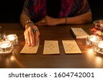 Small photo of Tarot reader picking tarot cards.Tarot cards face down on table near burning candles and crystal ball.Candlelight in dark.Tarot reader or Fortune teller reading and forecasting concept.