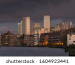 Small photo of London/UK - 11.18.2019: Moody clouds act as a backdrop to the office towers of Canary Wharf. Rotherhithe waterfront acts as a foreground.