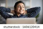 Happy satisfied indian woman rest at home office sit with laptop hold hands behind head, dreamy young lady relax finished work feel peace of mind look away dream think of future success concept - stock photo