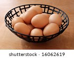 Fresh, golden brown eggs in metal basket on wood grain background. Concept - all eggs in one basket - stock photo