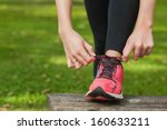 young woman tying the shoelaces ... | Shutterstock . vector #160633211