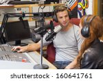 Small photo of Attractive content radio host interviewing a guest in studio at college