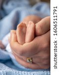 Small photo of premature newborn baby with mothers hand holding tiny feet represented by a reborn doll, background for copy space and text overlay