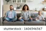 Small photo of Horizontal banner serene couple and little daughter sitting on sofa in lotus position closed eyes do meditation breathing technique in living room, keep calm, healthy life habits and lifestyle concept