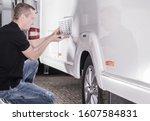RV Travel Trailer Check Before Vacation Season. Professional Recreational Vehicle Technician. - stock photo