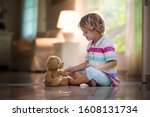 Child Playing With Teddy Bear....