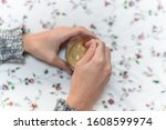 Small photo of Hands stirring a cup of coffee on a flowery background