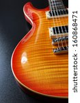 Closeup of electric guitar with cherry sunburst finish and flame maple top. - stock photo