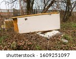 Small photo of Garbage, rubbish waste dumped in the environment. Wild landfill. Illegal dumping. The unauthorized, open dump of garbage. An old, broken fridge among bushes, thickets by a concrete fence in the city.