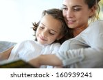 mom with little girl reading... | Shutterstock . vector #160939241