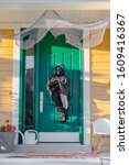 Small photo of A grim reaper decoration on a green front door