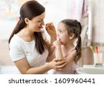 Small photo of Mother teaches her child daughter accurately brushing teeth