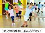 Small photo of Group of glad cheerful children practicing vigorous jive movements in dance class with female coach