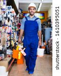 Small photo of Happy workman walking amongst racks in hardware store with paint and basket with tools