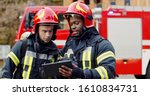Small photo of Portrait of two firefighters in fire fighting operation, fireman in protective clothing and helmet using tablet computer in action fighting.
