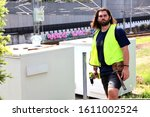 Brisbane QLD Australia January 09/2020 - Construction worker: Handyman does his work on a job site with high-vis vest, tool belt and drill in hand. Young bearded man ready for construction work. - stock photo