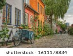 On a summer day a typical Danish Cargo bike, better known as Christiania Bike, is parked at the entrance of a house in a cosy, cobbled street conveying cozyness and cultural concept - Aarhus, Denmark