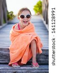 Cute little girl at beach covered with towel - stock photo