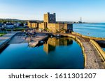 Medieval Norman Castle and harbor with boat ramp and wave breaker in Carrickfergus near Belfast, Northern Ireland, UK. Aerial view  in sunset light. Old power plant in the background