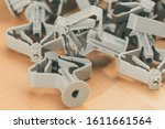 Small photo of Gray plastic dowels. Dowel on a wooden background. Fasteners. Construction details. Industrial background.