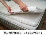 Small photo of Mattress Topper Being Laid On Top Of The Bed