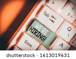 Small photo of Writing note showing We Re Hiring. Business photo showcasing recently employ someone or pay him to do particular job White pc keyboard with note paper above the white background.