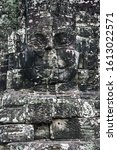 Small photo of bas relief face a smiling Buddha