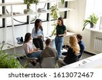 Small photo of Focused concerned diverse office employees gather together in modern light co-working space deliberating, discussing risks, solve business common problems, teamwork and partnership, brainstorm concept