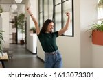 Small photo of Emotional student girl within walls of institute celebrating successful exam pass, high school or college admission, european employee raised hands feels happy by salary growth, got promoted concept