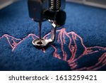 Small photo of intense macro closeup on embroidery of a light pink magnolia on classic blue boiled wool and needle, foot and needle bar of a embroidery machine - background with hoop and foreground blurry