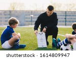 Small photo of Young Soccer Trainer Coach Explaining Tactic on Team Sports Tactics Board. Children During Soccer Football Coaching Session. Boys in Soccer Team Listening to Coach