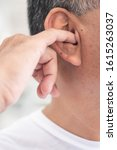 Small photo of man picking his ear with nasty, dirty habit; concept of ear wax picking, unhealthy habit, bad manner with smelly, stinky ear wax