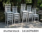 Exquisite wooden white chairs one on the other in garden, Albania