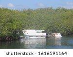 Broken Boat On Lagoon Shore