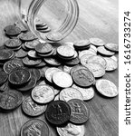 Small photo of Low Perspective View of a Pile of American Quarter Coins Spilling out of a Jar, Black and White