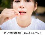 close up of woman putting pill... | Shutterstock . vector #1616737474