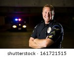A Smiling Police Officer With...