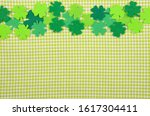 Small photo of Flat lay Happy St. Patrick's background mockup of handmade felt shamrock clover leaves on green napkin