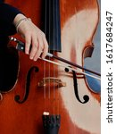 Small photo of Cellist player hands. Violoncellist playing cello on background of field. Musical art, concept passion in music. Classical music professional cello player solo perform