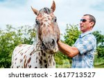 Man take care of his horse outdoor.Love between modern cowboy and animal on the ranch.Going for riding - stock photo