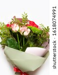 Small photo of Floral flat lay .Girl's hands holding beautiful flowers bouquet: bombastic roses, blue eringium, eucalyptus, isolated on white background. Flat lay, top view. valentine's day, march 8, mom's day
