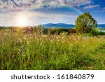 rays of the rising sun on top of a high mountain - stock photo